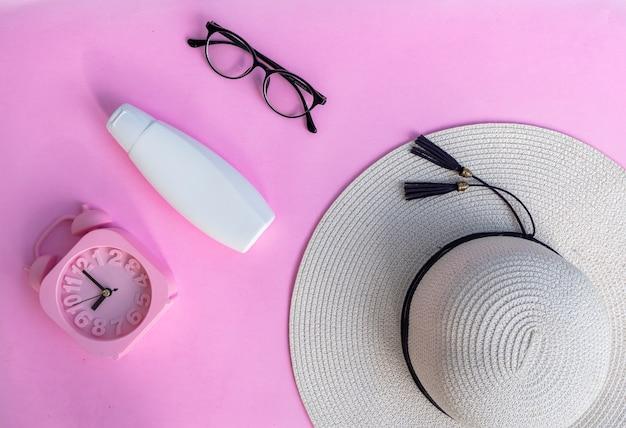 ピンクの紙の背景に白い化粧品ボトルコンテナ。自然な有機美容製品のコンセプト、ミニマリストの夏のスタイル