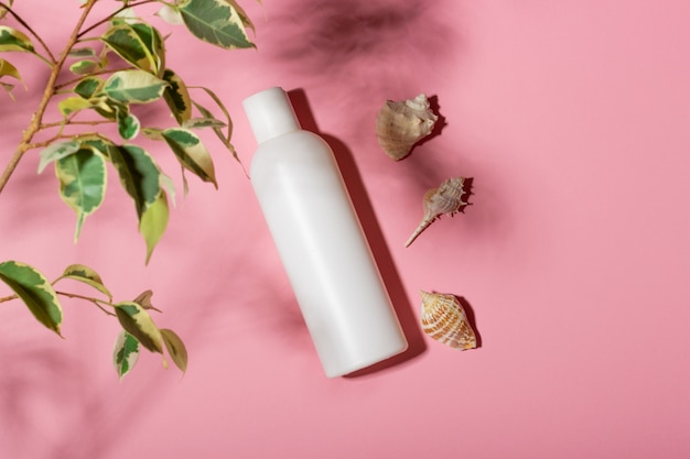White cosmetic bottle with face cream or lotion and telana against a pink background with seashells and shadows. sun cream, summer cosmetics.