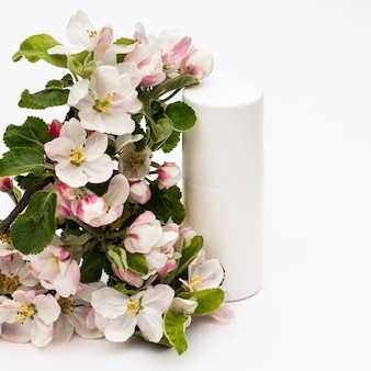 흰색 바탕에 배 꽃이 있는 흰색 화장품 병. 천연 유기농 화장품 개념입니다.