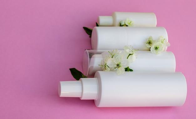 흰색 화장품 병, 목욕 폭탄, 수제 비누, 목욕 소금, 마사지 브러시, 스폰지, 분홍색 배경에 체리 꽃이 있는 면봉. 천연 유기농 화장품 개념입니다.