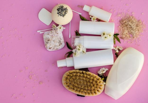 흰색 화장품 병, 목욕 폭탄, 수제 비누, 목욕 소금, 마사지 브러시, 스폰지, 분홍색 배경에 체리 꽃이 있는 면봉. 천연 유기농 화장품 개념입니다. 프리미엄 사진
