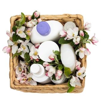 흰색 배경에 배 꽃이 달린 고리버들 바구니에 있는 흰색 화장품 병. 천연 유기농 화장품 개념입니다. 평면도
