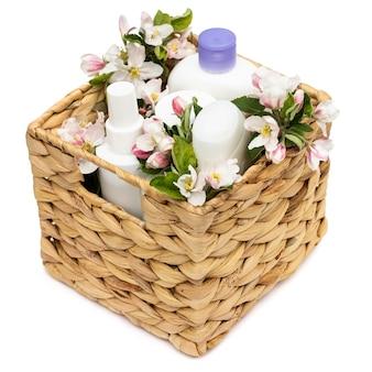 흰색 배경에 배 꽃이 달린 고리버들 바구니에 있는 흰색 화장품 병. 천연 유기농 화장품 개념
