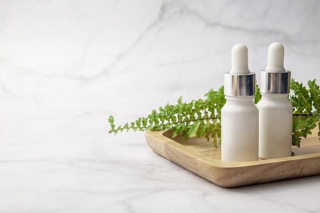 白い背景に緑の葉と白い化粧品ボトル