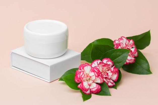 Белая косметическая баночка с кремом для ухода за кожей на светло-розовом