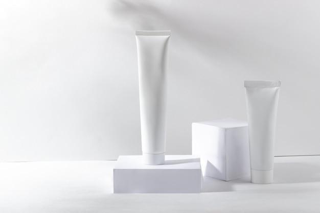 그림자와 함께 스탠드에 흰색 화장품 항아리입니다. 치약, 얼굴 및 바디 크림. 피부 관리를 위한 전문 화장품. 유기농 화장품.