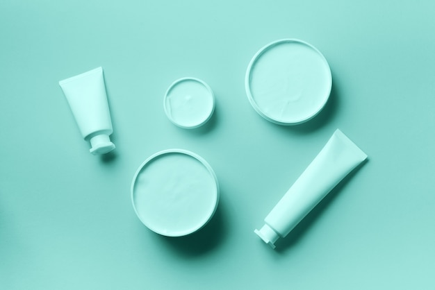 White cosmetic jar, tube, bottle and tropical monstera leaf