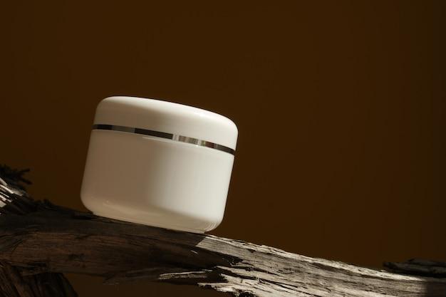 Белая косметическая банка с кремом на бревне и с жесткими тенями