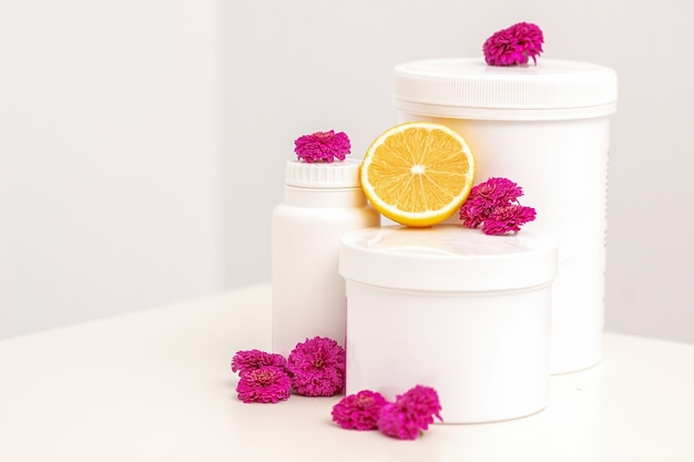 White cosmetic jars, containers, bottle with fresh lemon and chrysanthemums flowers