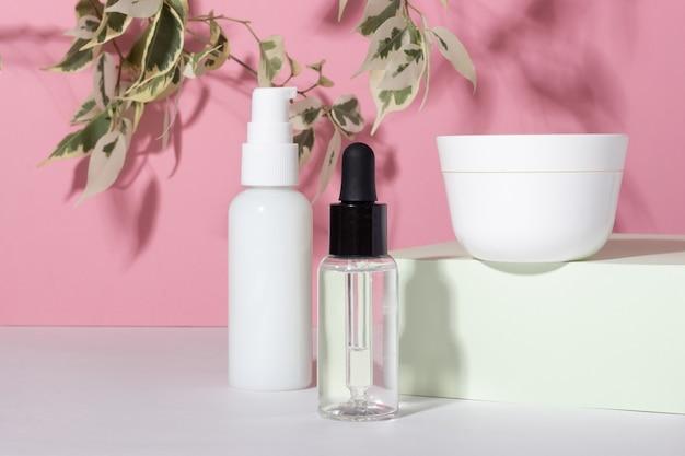 스탠드에 흰색 화장품 항아리입니다. 크림, 로션, 혈청 및 안면 마스크용 플라스틱 용기. 환경 친화적인 유기농 화장품의 개념.