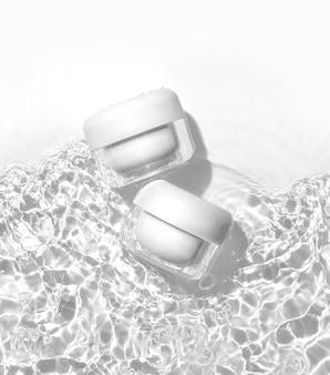 水面に白い化粧品の瓶。夏の水プールの新鮮なコンセプト。フラットレイ、上面図。