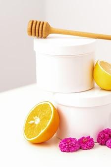 흰색 나무 꿀 스틱, 신선한 레몬, 국화 꽃과 흰색 화장품 항아리