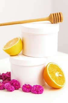 White cosmetic jars with a wooden honey stick, fresh lemon, and chrysanthemums flowers on white background with copy space. blank space for branding mockup beauty product