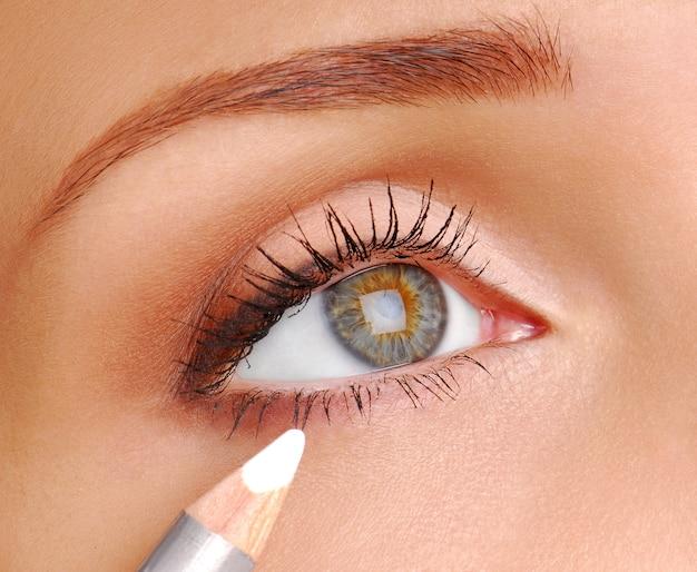 Белый косметический карандаш. инструмент для макияжа. глаз женщины крупным планом.