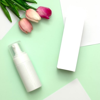 White cosmetic products and pink tulip flower on mint green and white paper background.