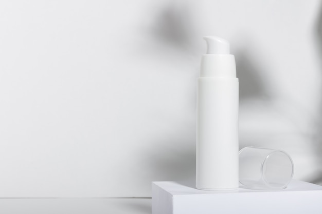 White cosmetic tube for cream, lotion, serum or face mask on the runway with leaf shadows. professional cosmetics for skin care. organic cosmetics.