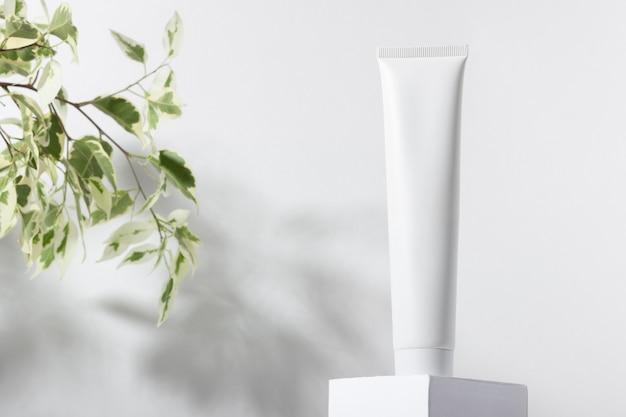 잎과 그림자가 있는 스탠드에 있는 흰색 화장품 튜브. 치약, 얼굴 및 바디 크림. 스킨 케어 제품이 있는 여성용 화장품 튜브. 유기농 화장품. 공간을 복사합니다.