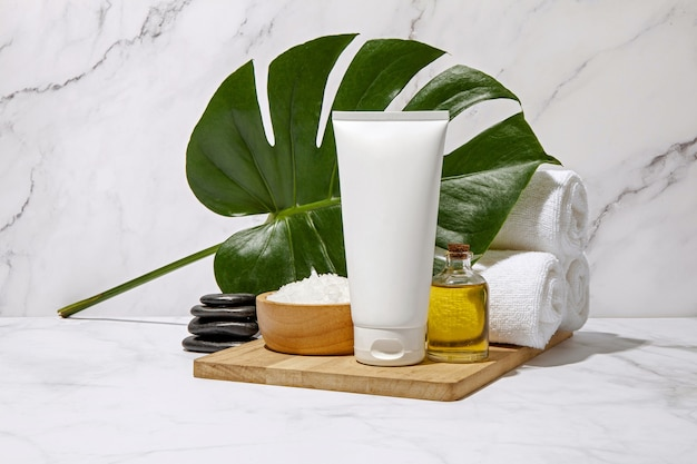 White cosmetic tube with spa element and towel on marble