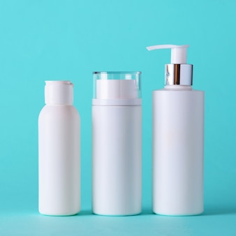 White cosmetic tubes on blue background with copy space