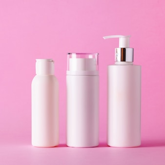 White cosmetic tubes on pink background with copy space