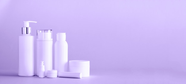 White cosmetic tubes on trendy violet color background
