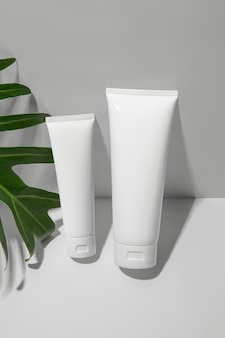 White cosmetic tubes with green leaf on white background. minimalist style .