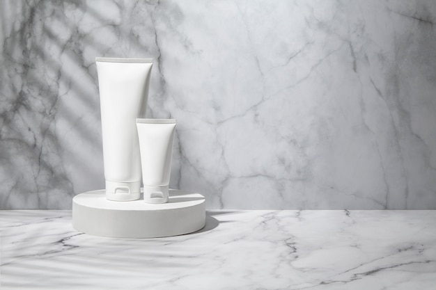 White cosmetic tubes with palm leaf shadow on marble