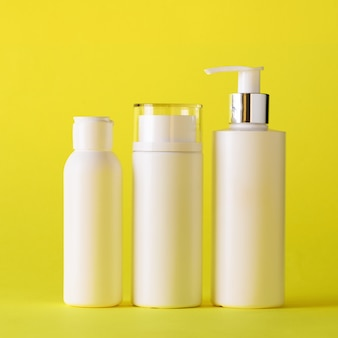 White cosmetic tubes on yellow background with copy space.
