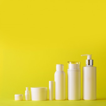 White cosmetic tubes on yellow background with copy space