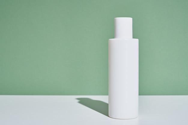 Макет бутылки белой косметики на зеленом фоне