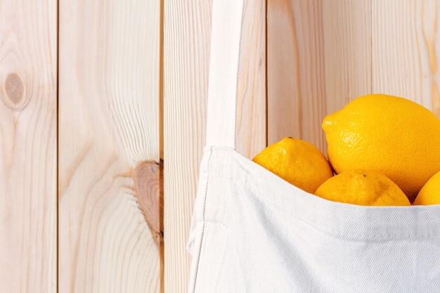 木製の壁のクローズアップに対してレモンでいっぱいの白い綿のバッグ