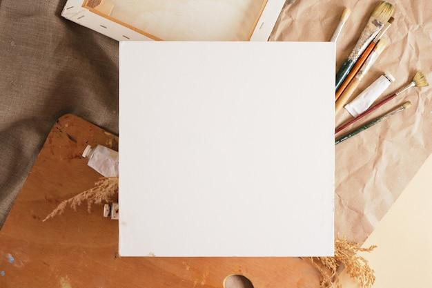 Белый хлопковый холст на картоне и различные инструменты художника, макет фона, пустой квадратный холст, место для копирования