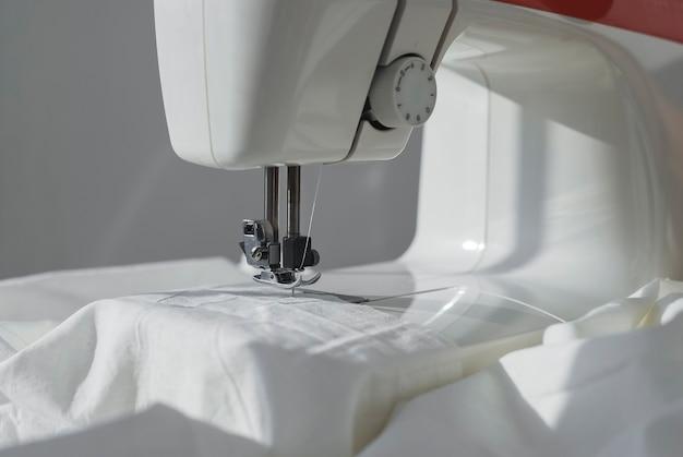 Белая хлопчатобумажная ткань на швейной машине крупным планом