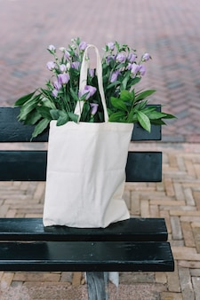 White cotton handbag with beautiful purple eustoma flowers in the black bench