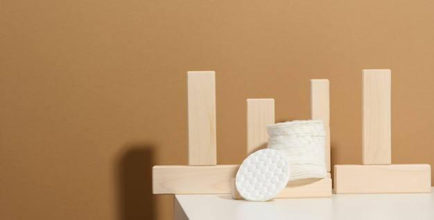白いテーブルの上の白い綿のスポンジ。美容、医療、化粧品業界向けのデザイン