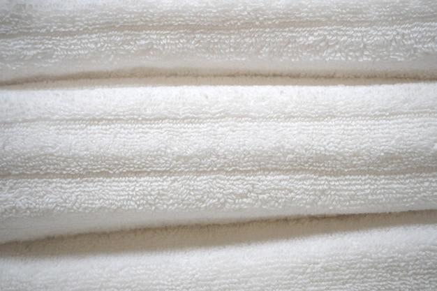 서로 위에 쌓인 흰색 면 수건을 닫습니다.