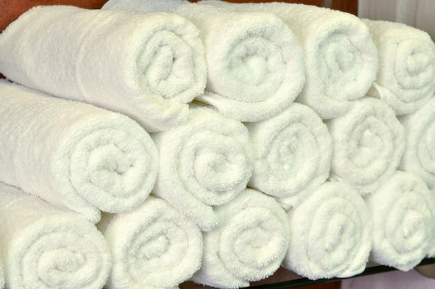 White cotton towels texture background. white clean towels on bathroom shelf in spa hair or beauty salon