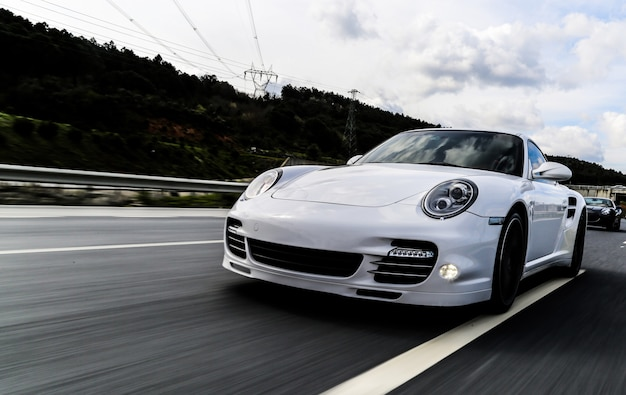 White coupe driving on the road.
