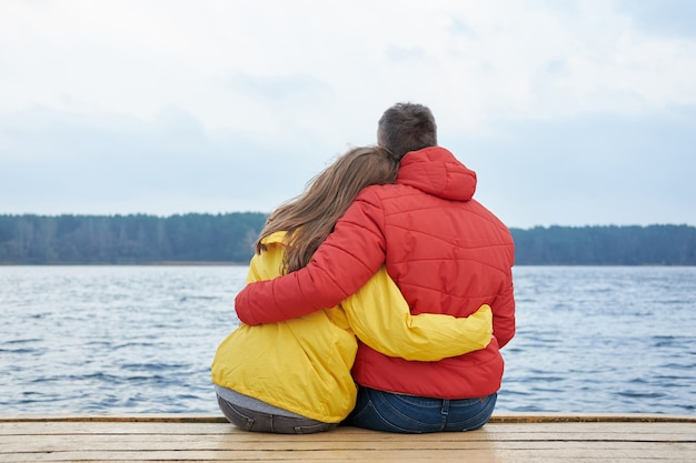 White couple in yellow and red jackets sitting and hugging each other on the pier near lake in cloudy autumn day.