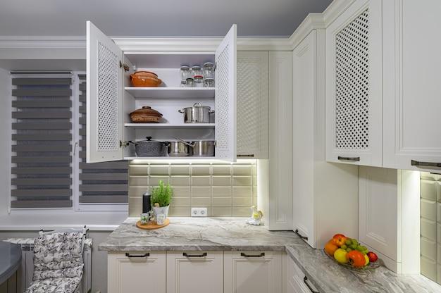 Белый уютный и удобный современный классический интерьер кухни с деревянной мебелью, шкаф открытый, посуда на полках