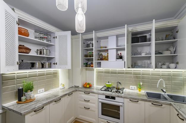 Белый уютный и удобный современный классический кухонный интерьер с деревянной мебелью, дверцы шкафов открыты, посуда на полках.
