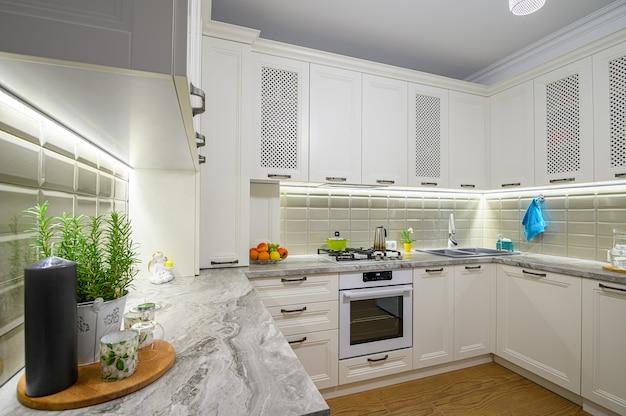 Белый уютный и удобный современный классический интерьер кухни с деревянной мебелью