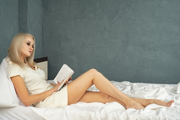 White cozy bed and a beautiful girl, reading a book, concepts of home and comfort, place for text