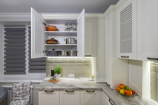 White cozy and comfy contemporary classic kitchen interior with wooden furniture, cabinet is open, kitchenware at shelves