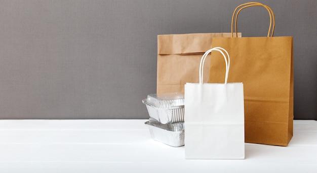 白いテーブルの上の白いクラフト紙袋と食品容器。フードデリバリーサービス。持ち帰り用食品