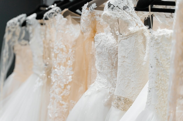 Белое свадебное платье кремового цвета на вешалках в свадебном салоне.