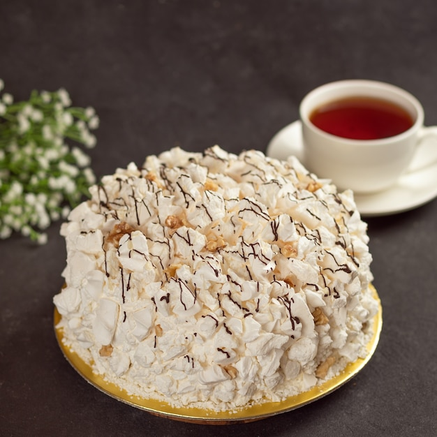 White cream cake with cup of tea close up