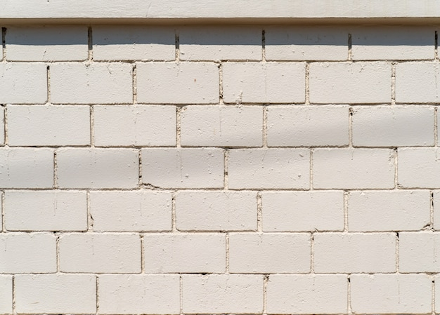 背景の屋外フィールドにレンガ模様のホワイトクリームセメント壁。