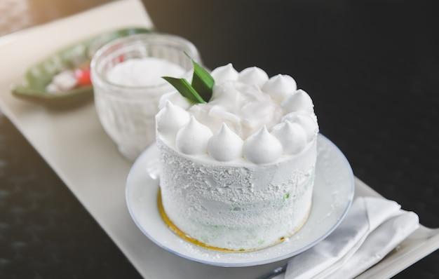 White cream coconut cake with indoor lighting.