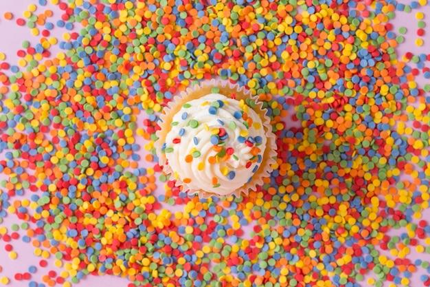バラの高品質の写真に色を振りかける白いクリームカップケーキ